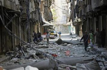 Residents walk on rubble in a damaged street in Aleppo's district of Bustan al-Basha